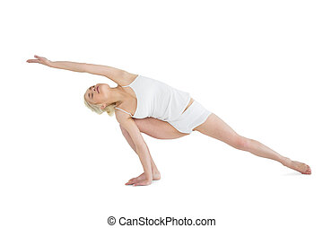 Full length of a sporty young woman practicing yoga over...