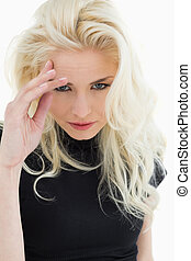 Portrait of a tensed casual young blond standing over white...