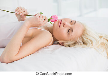 Side view of a pretty woman in bed with rose - Side view of...