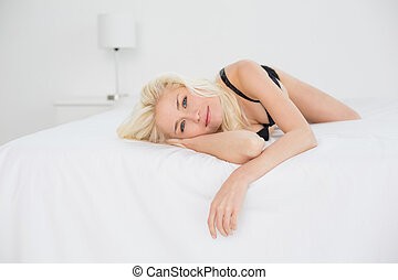 Portrait of young blond lying in black bra on bed - Portrait...