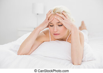 Tensed pretty woman lying in bed - Tensed pretty young woman...