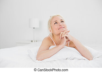 Young woman with joined hands lying in bed - Relaxed pretty...