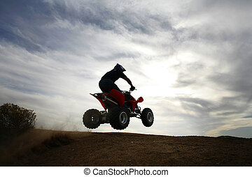 Into the sky - A 4 wheeler aka Quad jumps off a dirt lip...