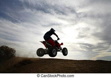 Into the sky - A 4 wheeler aka Quad jumps off a dirt lip...