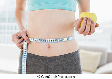 Mid section of woman measuring waist with apple in hand -...