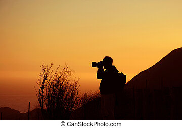 Photographer - Silhouete of a photographer holding a long...