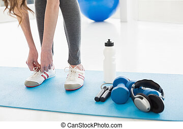 Woman tying shoes with sporty equipment on floor - Low...
