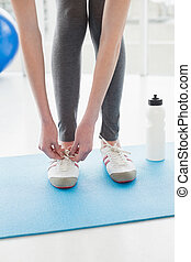 Low section of woman tying shoes with water bottle on floor...