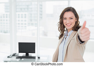 Elegant smiling businesswoman gesturing thumbs up in office...