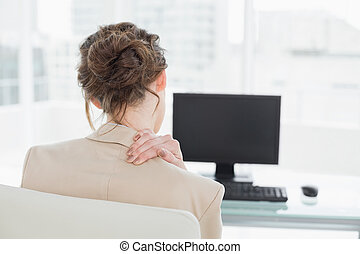 Rear view of businesswoman with neck pain in office - Rear...