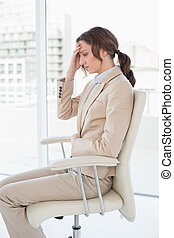 Side view of businesswoman suffering from headache in office...