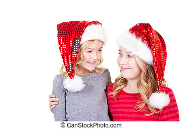 Sisters or two young girls wearing Santa hats
