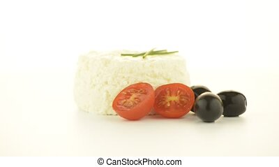 Cottage cheese with tomato and olives rotating on white...