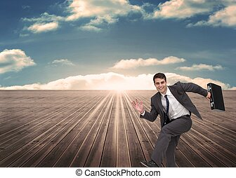 Cheerful man holding a suitcase and running - Composite...