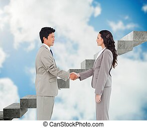 Side view of hand shaking trading partners - Composite image...