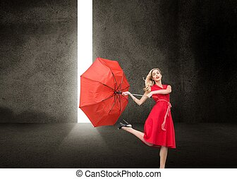 Beautiful woman wearing red dress holding umbrella -...