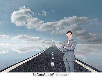 Assertive businessman standing on street - Composite image...