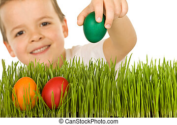 Happy boy with easter eggs in the grass