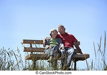 Happy old couple sitting on a bench