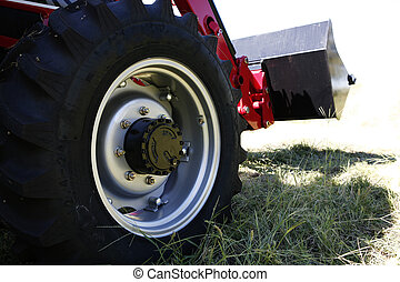Tractor - Large tractor wheel with loader background