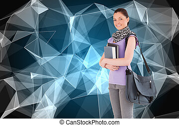 Composite image of attractive student holding books and her bag while standing against a white background