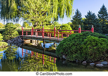 Decorative Red Bridge over Placid Pond with Asian Features