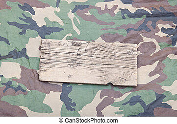 close up of an empty wooden sign on military fabric
