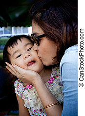 girl children and mom kissing on cheek with lovely face