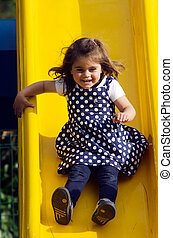 little girl slides in playground - little girl ,three years...