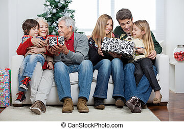 Family With Christmas Presents Sitting In House - Full...