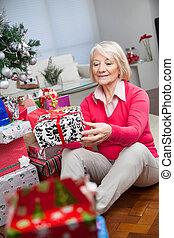 Senior Woman Looking At Christmas Gift