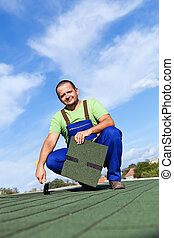 Worker installs bitumen roof shingles