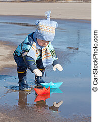 Little boy plays with paper ships in a puddle