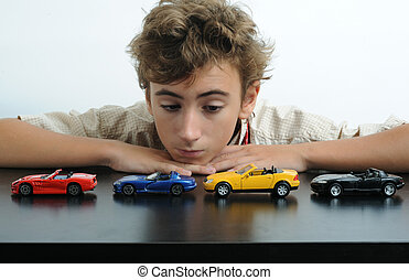 Cars - A teen playing with cars on a table