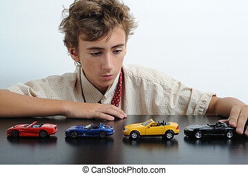 Race - A teen playing with cars on a table