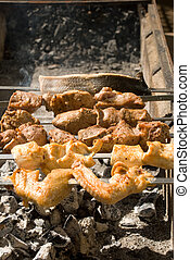 Mutton, a chicken and a fish on a barbecue