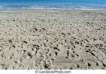 footprints on a beach, at the background the sea
