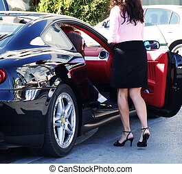 prominent - a woman gets out from an expensive car