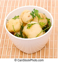 Boiled potatoes with parsley on a bamboo napkin