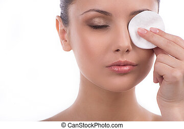 Removing eye make-up Beautiful young woman using cotton ball...