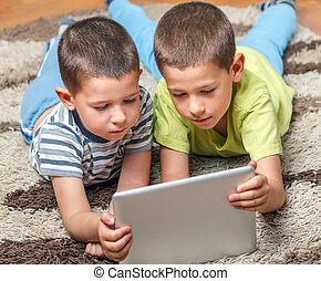 Brothers on the floor using tablet