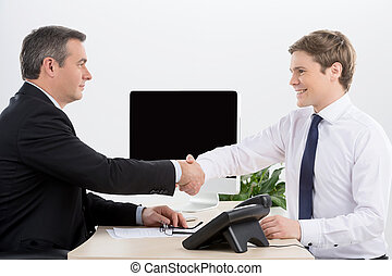 Handshaking Two cheerful men in formalwear shaking hands and...