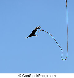bungee jumping - silhouette of a man jumping with a rope on...