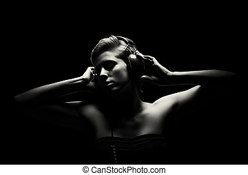 gorgeous woman in black and white listening to music -...