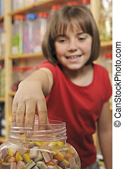 child in sweet shop - young girl grabbing sweets from a jar...
