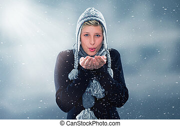 young woman blowing snow off her hands - young woman in...