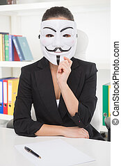 Businesswoman in mask. Young woman in formalwear holding mask on her face while sitting at her working place