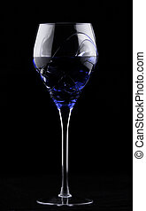 Wine glass with blue potion on dark background poison