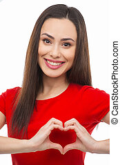 Heart shape. Beautiful young woman holding her hands in heart shape and smiling while isolated on white