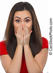 Shocked woman. Surprised young woman covering mouth with hands and looking at camera while isolated on white